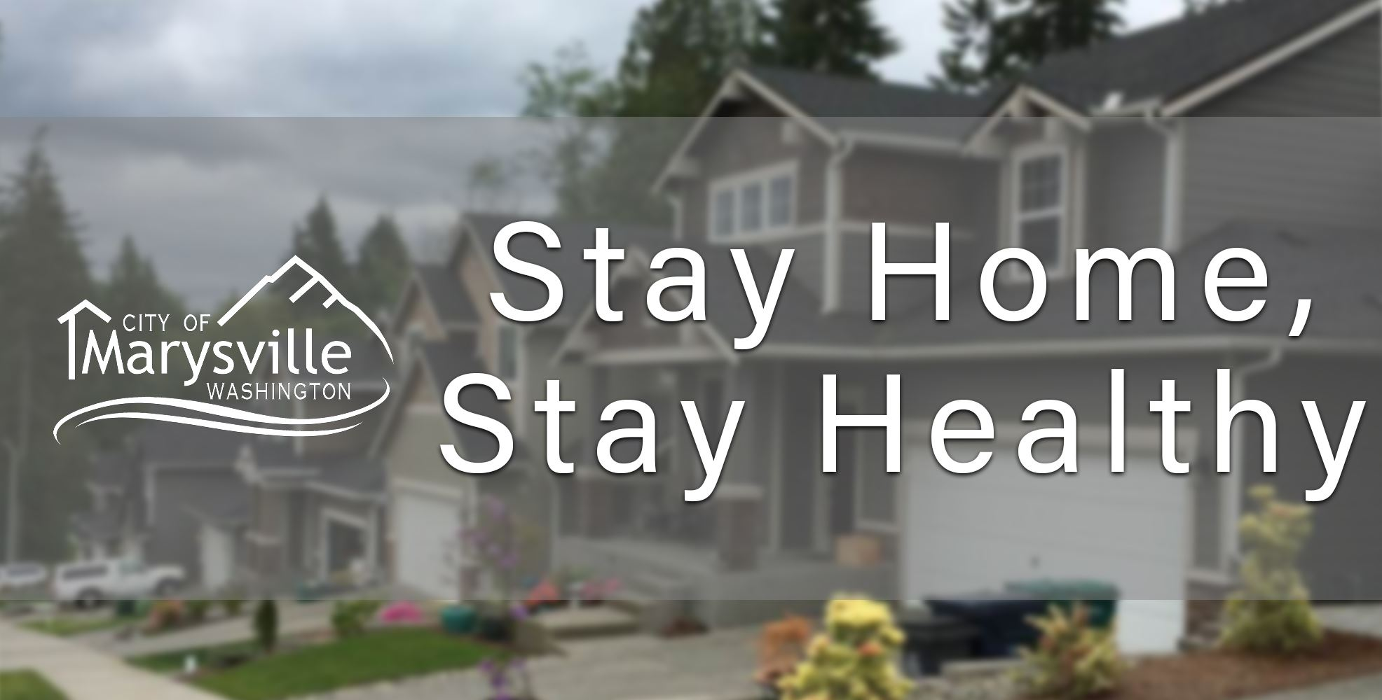 "A photo of homes is overlayed by text saying, ""Stay Home, Stay Healthy"""