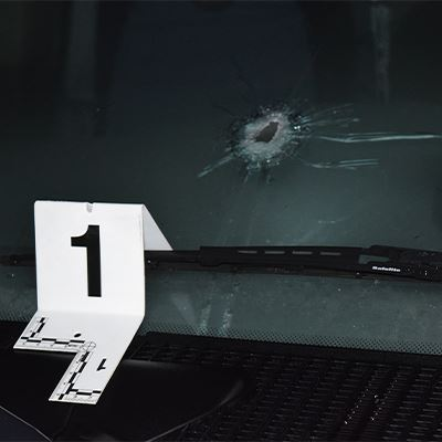 A marker sits on the front window of a car where there is a bullet hole