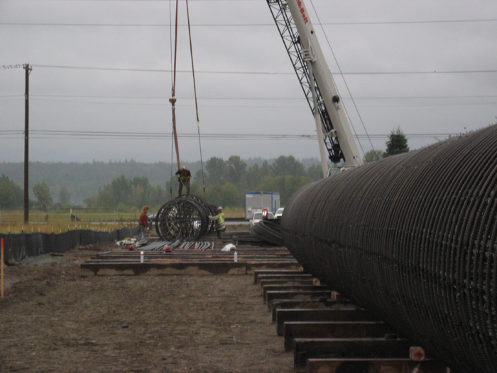 Workers prepare steel rebar cages for bridge foundation shafts